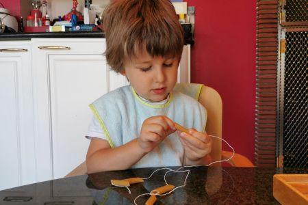 Un enfant enfile des pâtes pour faire une activité manuelle originale.