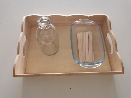 Installez sur un plateau de vie pratique un contenant rempli de bâtonnets et mettez en un autre dans lequel l'enfant pourra les insérer.