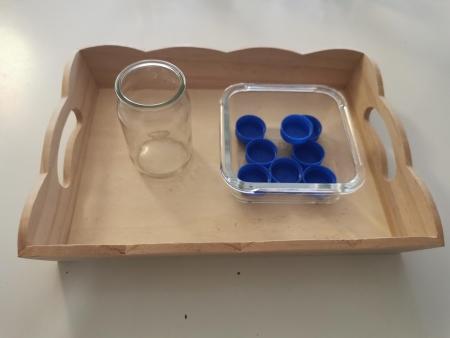 Installez sur un plateau de vie pratique un contenant en verre rempli de bouchons de bouteille d'eau, et un contenant vide au diamètre un peu plus large que celui des bouchons.