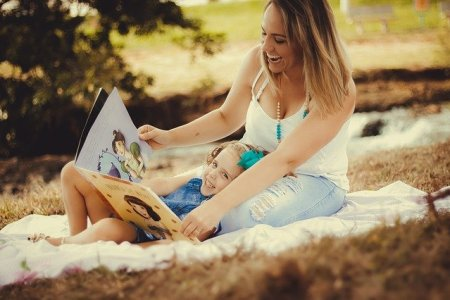 une maman lit un album de littérature enfantine à son enfant pour créer du lien.