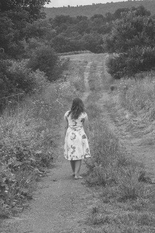une fillette marche nus pieds le long d'un chemin.
