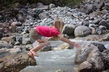 Un enfant traverse un ruisseau pieds nus en marchant sur des rochers.