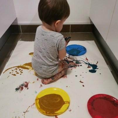 Un enfant mélange de la peinture sur ses mains.