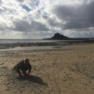 Porth Jewellery's founder beach combing for seaglass on the beach at Marazion with St Michael's Mount in the background.