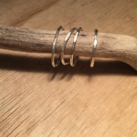 4 thin silver stacking rings on a piece of driftwood.