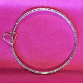 Hammered silver bangle with a heart silver attached, sitting on a hot pink background
