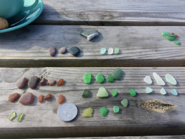 Seaglass lined up on a table after a beach combing trip.