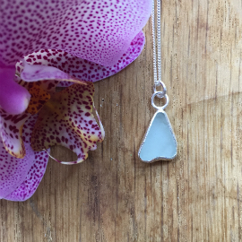 Light aqua Mermaids Tail necklace next to an orchid flower.