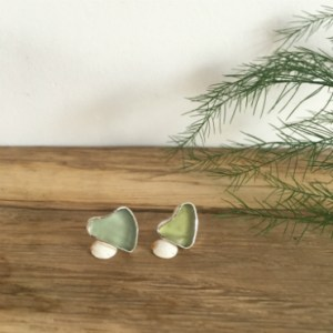 Two seaglass hearts set into silver to make a pair of studs. One is a light olive colour, the other a grey-green.