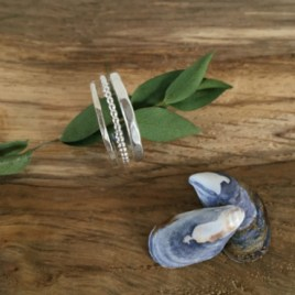 3 silver stacking rings featuring one thin, one beaded and one wider silver band.