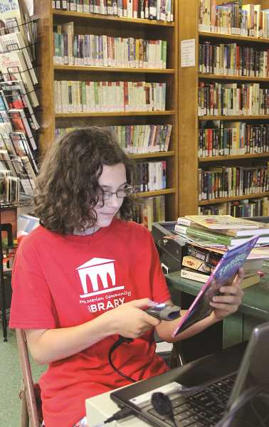 LINDSAY KEEFER - North Marion Community Library volunteer Nicole Scott, 12, of Canby, adds recently-donated books to the library system.