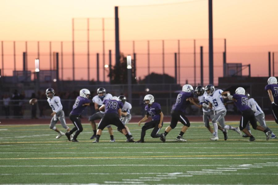 %2312+quarterback+and+sophomore+Brandon+Yue+makes+a+pass+to+one+of+his+teammates+while+the+Saddleback+Warriors+attempt+to+stop+the+Bulldogs.+
