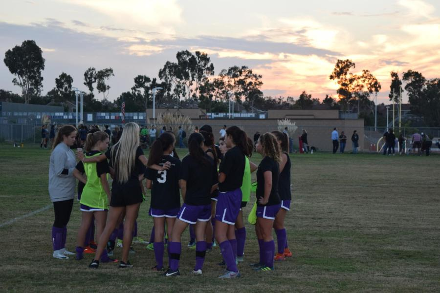 JV Girls' Soccer huddles before an evening matchup against University High.