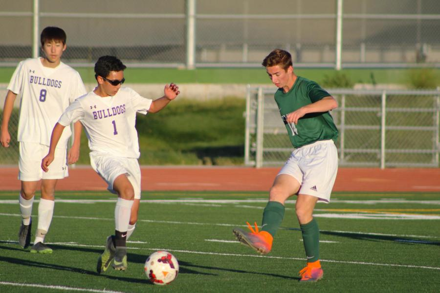 Sophomore and center mid Mustafa Hassan works around opposing players to keep the ball in his possession and passes to his teammates.