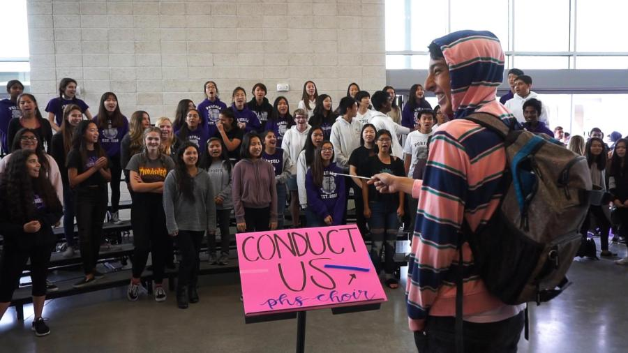 Sophomore Roham Ghiasi radiates pure joy as he conducts the choir during the lunchtime activity.