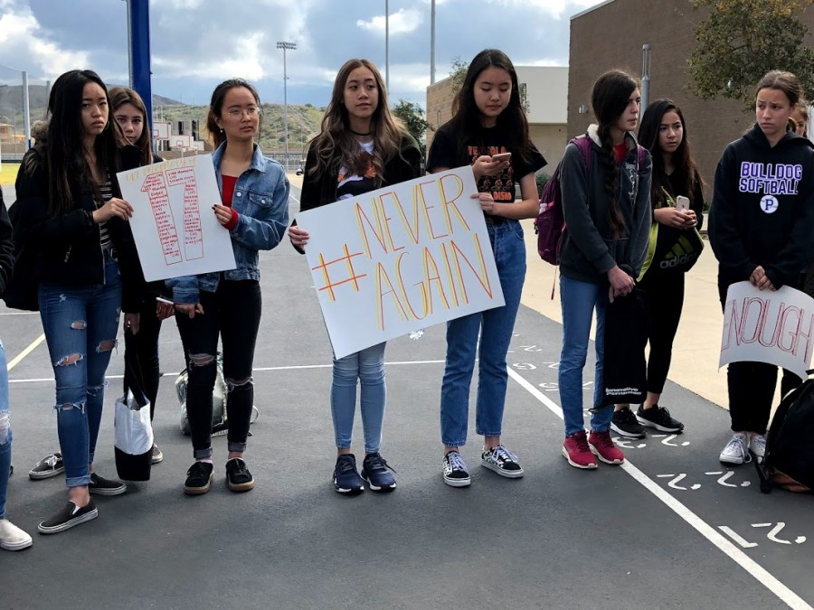 """Freshman Kelthie Truong holds a sign that says """"#NeverAgain,"""" while freshman Kristen Ok keeps track of the 17 minutes as she reads off the names of those killed in the Florida shooting."""