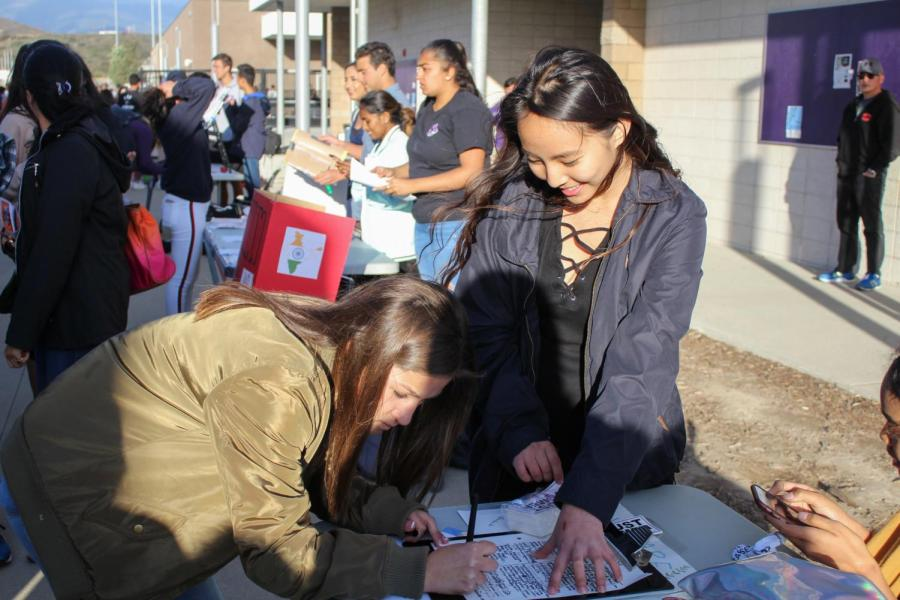 Sophomore Stephanie Tang helps an incoming freshman sign up for the National Organization of Women club. Students were able to watch performances from the visual and performing arts department and learn about the available activities on campus.