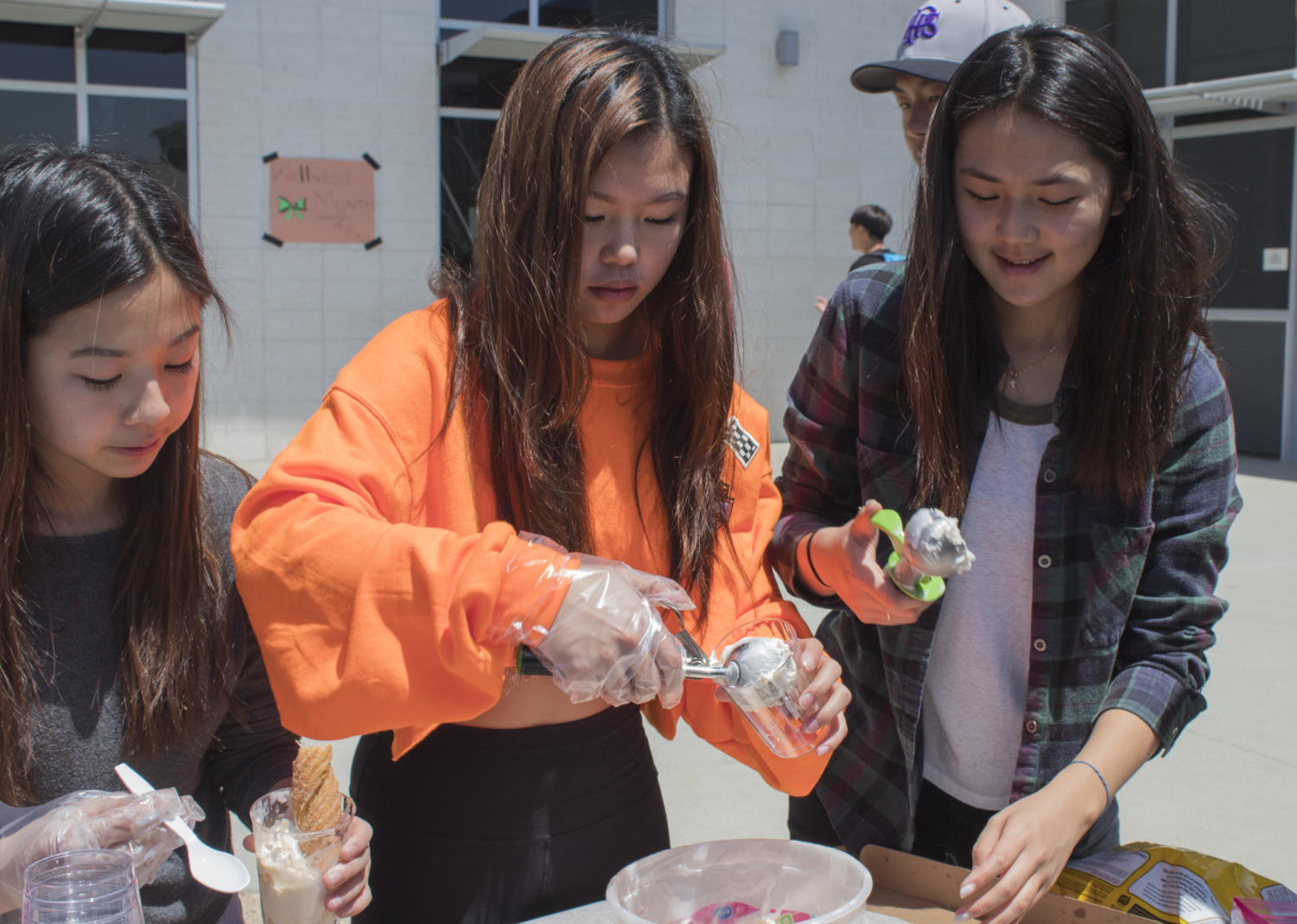 Club members and sophomores Annika Lai, Miranda Wang and Lauren Hwang scoop out ice cream and churros in return for tickets for Create the Change Club. Hwang founded the club in order to help families in Peru, and plans on using the money earned from Club-a-Palooza to purchase lotions, vitamins and other materials to help the children in need.