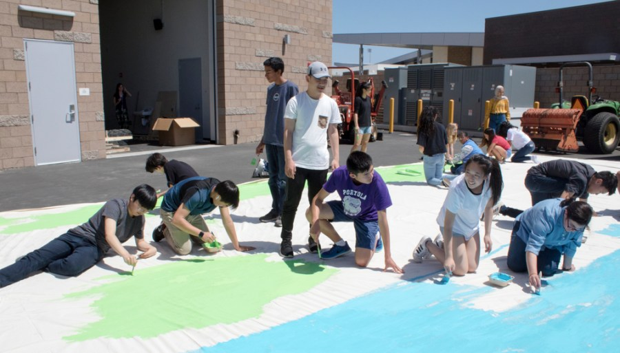 """The technical theater crew paints a backdrop for the upcoming """"Wizard of Oz"""" musical, utilizing the color wheel and brush strokes to create a realistic, whimsical set."""