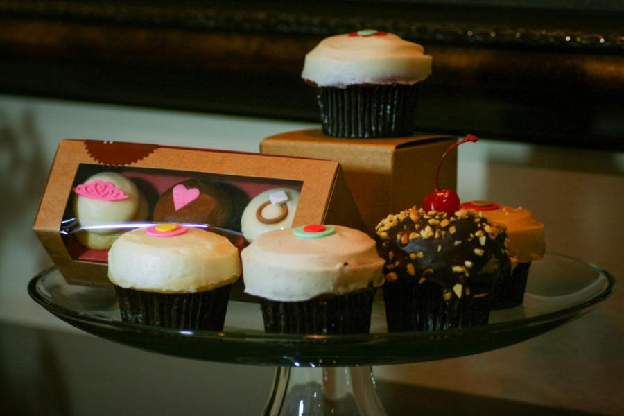 Displayed above from right to left are lemon, carrot, banana dark chocolate and salted caramel cupcakes. The original red velvet cupcake is shown on top.