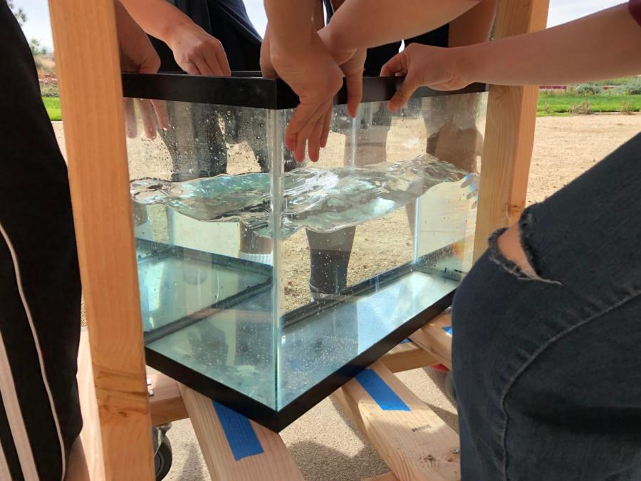 Students from the 2017-18 Living Earth classes collaborate around a fish tank resting upon a wooden structure that they constructed themselves. The structure contains wheels that students drilled on with help from principal John Pehrson in the Innovation Lab.