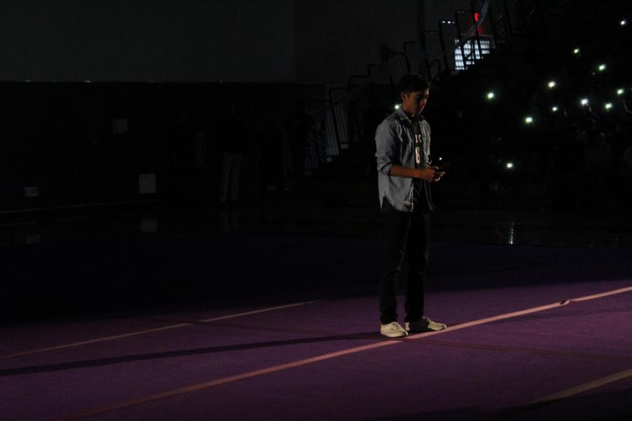 In the pitch-black gym, sophomore Ian Aros waits in the spotlight ready to hit the high notes of the national anthem.