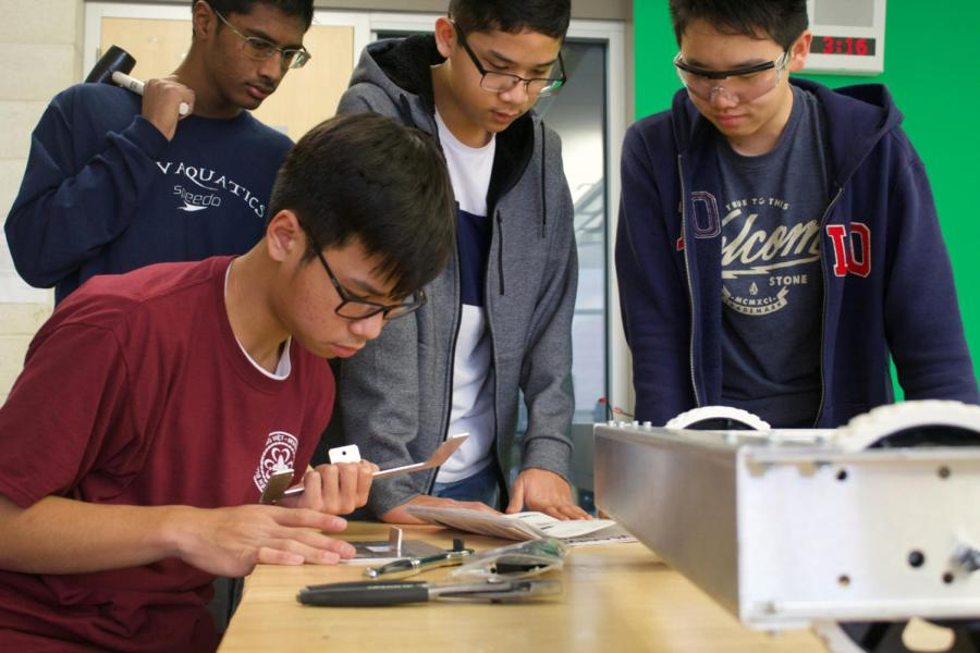 FIRST+Robotic+Team%E2%80%99s+sophomore+Trung+Huynh+builds+the+structure+for+the+battery+compartment%2C+finishing+the+final+parts+of+the+robot%E2%80%99s+base%2C+while+sophomore+Neil+Lin+and+freshmen+Goshanraj+Sandal+and+Ryan+Bascos+prepare+for+assistance.+The+robot+is+designed+to+secure+the+most+game+pieces+possible+into+the+rocket+ship%E2%80%99s+holes+in+the+time+slot+allowed%2C+in+a+competition+aligned+with+the+%E2%80%98Deep+Space%E2%80%99+theme.