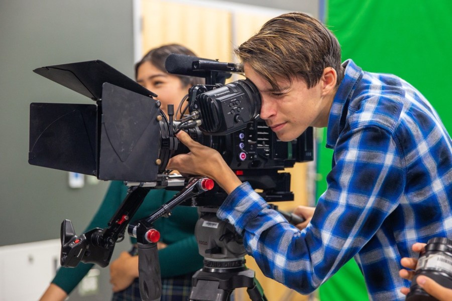 Sophomore Andrew Harriger looks through the camera to visualize and adjust his shot during the FilmEd summer camp. According to Ms. Murphy, the experience that the students gain using more expensive equipment enhances their abilities with the school equipment.