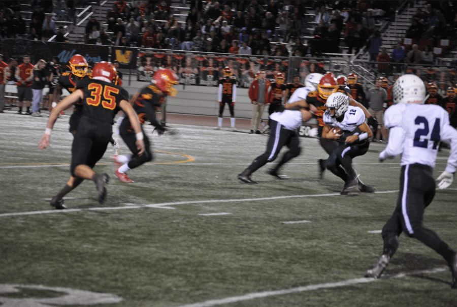 Quarterback Brandon Yue scrambles past the Warrior defense on second down. Yue was named MVP of the game by Coach Abe for his stellar performance on both offense and defense.