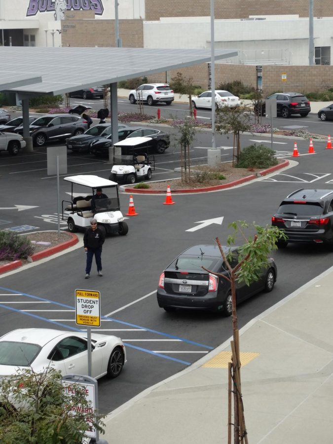 Campus Control Assistants Kathy Elgohary and George Mares supervise the drop-off line to keep a constant flow of traffic. This year, there are more student drivers at Portola High than ever, causing more traffic to build up around campus and on Irvine Blvd. in the morning.