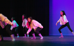 """Dance 3 students crouch down during the solo section of the piece, """"Crybaby,"""" choreographed by sophomore Mia Zappala. Choreographers were also responsible for costume design and stage lighting, fine-tuning these elements to enhance their overall performance."""