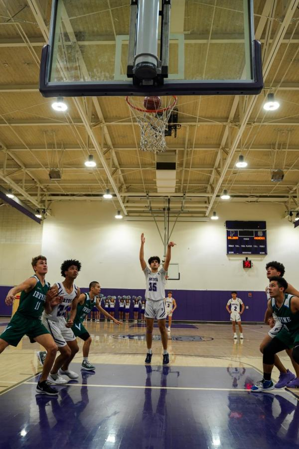 Bulldogs and Vaqueros swarm the paint for the rebound as Forward and Senior Mohsen Hashemi shoots a free throw. The Bulldog's ability to draw shooting fouls was a key factor in their win against Irvine High. The final score was 65-45.
