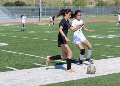 Right forward and junior Krista Calkins uses her body to protect the ball from the Vaqueros' defender with hopes of finding another forward to drive it up the field. Calkins was substituted in for Song in the last seven minutes of the half.
