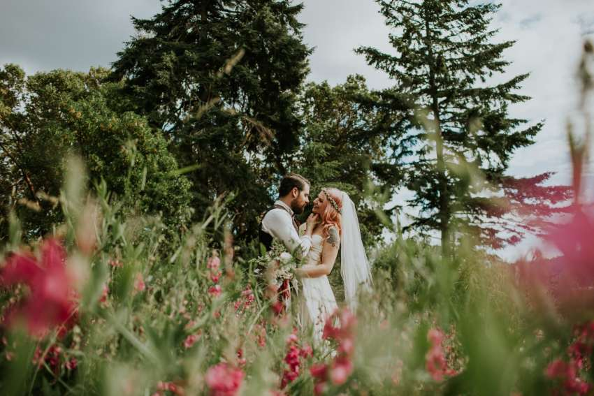 bride and groom in flower field orcas island wedding