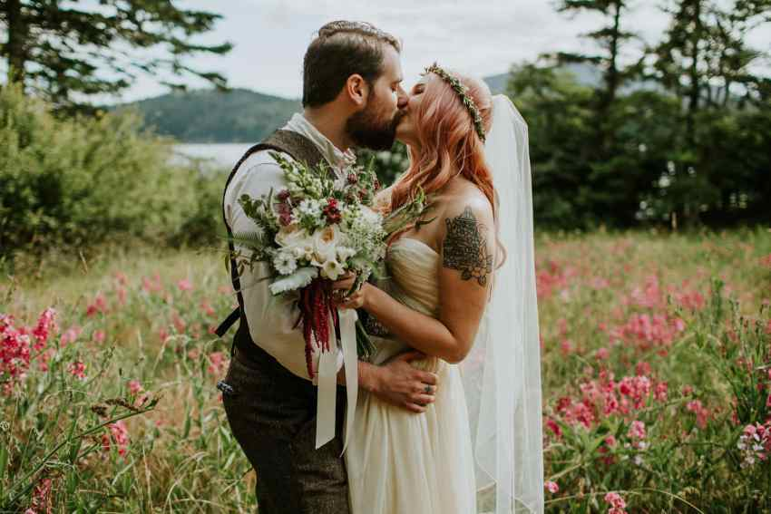 groom kissing bride with pink hair flower field