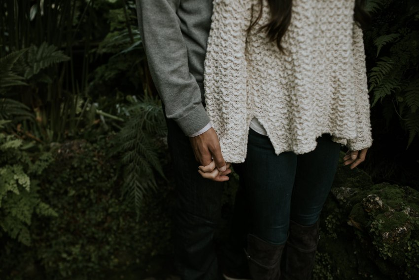 couple holding hands in greenhouse