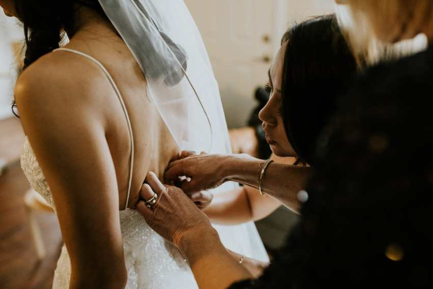 maid of honor mother helping daughter into wedding dress