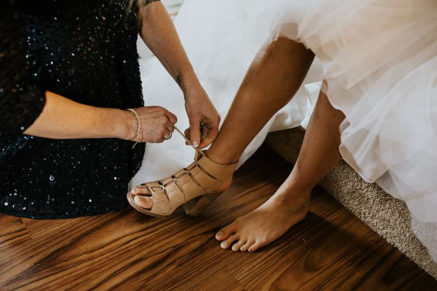 mother helping bride into wedding shoes