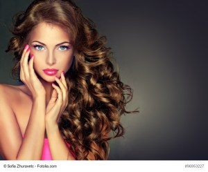 Beautiful model brunette with long curled hair . Hairstyle wavy curls . Crimson nails manicure .Makeup color fuchsia .