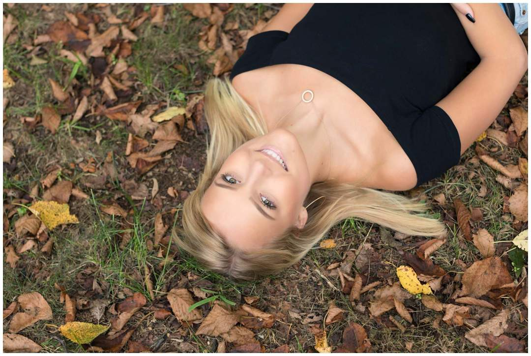 Outdoor senior portrait with autumn leaves