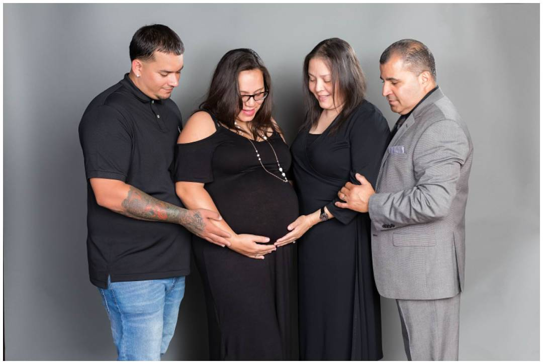 Maternity photos with family in studio on grey background
