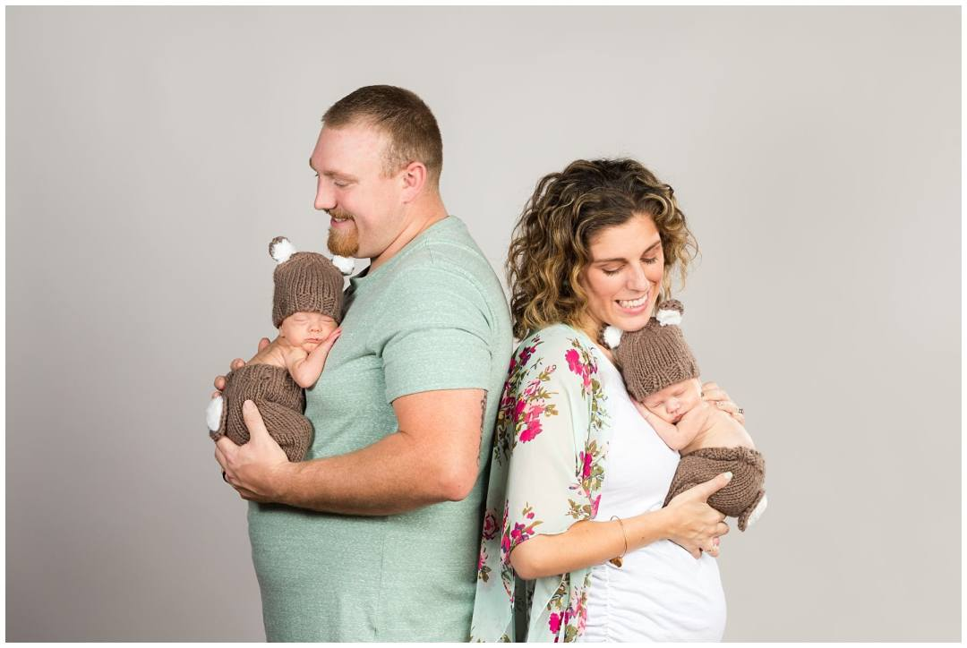 newborn twins in knitted deer outfits with parents