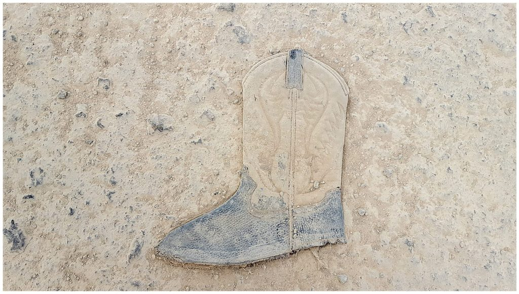 monochromatic image of boot in dirt