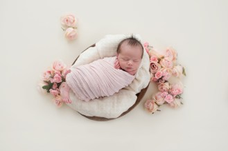 baby in spring flowers pink