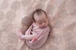 baby wrapped in dusty rose