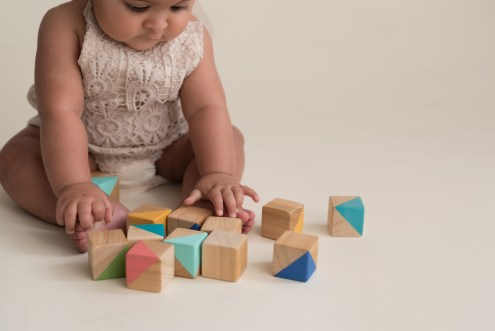 baby girl playing with wood blocks