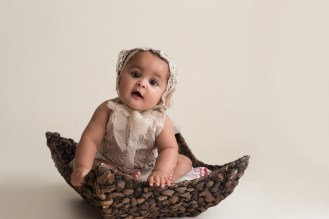 vintage baby girl sitting in basket
