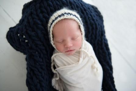 baby boy in navy bonnet
