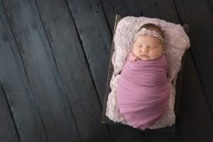baby wrapped on dark barn wood