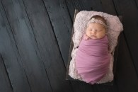 baby wrapped on dark barn wood